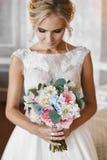 Modernes und elegantes blondes vorbildliches Mädchen mit stilvoller Heiratsfrisur und mit hellem Make-up im weißen Kleid der Spit stockbilder