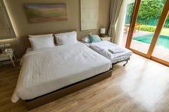Modernes weißes Schlafzimmer auf Holzfußboden Stockfotos