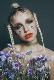 Modernes weibliches Porträt im Studio mit dem Haar, Make-up und Blumen Stockbilder