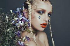 Modernes weibliches Porträt im Studio mit dem Haar, Make-up und Blumen Lizenzfreie Stockfotos