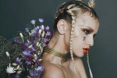 Modernes weibliches Porträt im Studio mit dem Haar, Make-up und Blumen Stockbild
