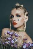 Modernes weibliches Porträt im Studio mit dem Haar, Make-up und Blumen Stockfotos
