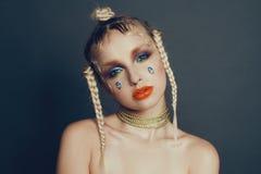 Modernes weibliches Porträt im Studio mit dem Haar, Make-up und Blumen Lizenzfreies Stockfoto