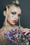 Modernes weibliches Porträt im Studio mit dem Haar, Make-up und Blumen Lizenzfreie Stockbilder