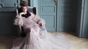 Modernes weibliches Porträt netter Dame im rosa Kleid zuhause stock footage