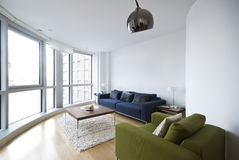 Modernes Wohnzimmer mit Fußboden zu den Deckenfenstern Stockfotografie