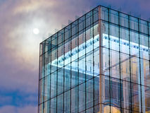 Modernist Moon. A moon looms over a modernist glass building during the twilight hour stock photography