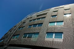 Modernist office building. A modern `spaceship` design office building gleams in the summer sun against a blue sky royalty free stock photos