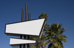 Modernist Sign. Quintessential Palm Springs -- a blank, white and black modernist sign in front of palm trees and a clear blue sky Royalty Free Stock Image