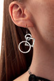 Modernist silver ear ring. Modernist silver earring with geometric figures hanging on the ear of a girl royalty free stock photo