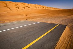 Modernity versus nature concept - end of civilisation. Beginning of desert. Modern paved highway ending up in sand dunes Royalty Free Stock Photos