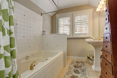 Modernized bathroom with outset bathtub, and triangle cabinets. Royalty Free Stock Photos