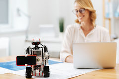 Modernized robot demonstrating abilities indoors. Helping people in ordinary stuff. Skilled automatic helpful robot standing on the table in the office and Royalty Free Stock Photos