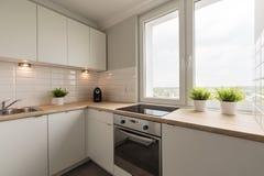 Modernized and spacious kitchen. Horizontal photo of modernized and spacious kitchen in creamy colors Stock Image