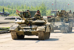 Modernized tank T-72 and convoy in motion. Russia Royalty Free Stock Photo