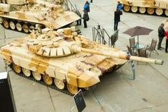 Modernized tank T-72. Russia. Nizhniy Tagil, Russia - September 25. 2013: Visitors examine military equipment on exhibition range. On foreground T-72. Modernized Royalty Free Stock Photography