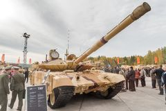 Modernized tank T-90s. Russia. Nizhniy Tagil, Russia - September 25. 2013: Visitors examine military equipment on exhibition range. On foreground T-90s Stock Photos