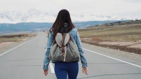 Moderno adolescente da moça que anda na estrada Com uma trouxa do acampamento e um revestimento do jérsei Contra o contexto de ne vídeos de arquivo