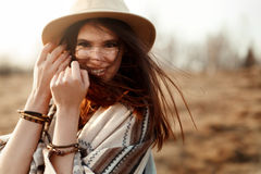 Moderno bonito da mulher do boho, poncho sorrindo, vestir chapéu e no por do sol nas montanhas, emoções verdadeiras, espaço para  imagens de stock