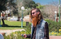 moderno com a barba vermelha que olha em seu telefone celular fotos de stock