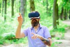 Moderno com jogo móvel dos auriculares no ar fresco Homem com vidros do desgaste VR da barba em exterior ensolarado Homem farpado Foto de Stock