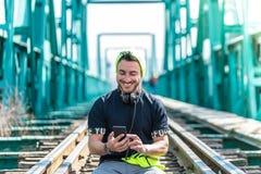 Moderno considerável Guy Using o telefone celular e os fones de ouvido vestindo Assento nas trilhas do trem imagem de stock royalty free