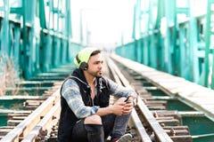 Moderno considerável Guy Using o telefone celular e os fones de ouvido vestindo Assento nas trilhas do trem imagens de stock royalty free