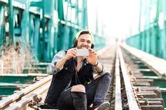 Moderno considerável Guy Using o telefone celular e os fones de ouvido vestindo Assento nas trilhas do trem fotografia de stock royalty free