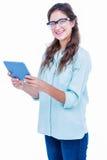 Moderno consideravelmente geeky que sorri na câmera e que guarda a tabuleta Fotografia de Stock
