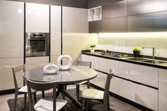 Moderno construido en cocina con la mesa de comedor circular foto de archivo libre de regalías