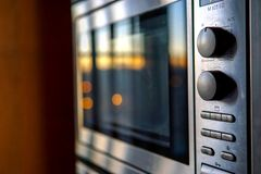 Moderno construido en dispositivos de cocina en acero inoxidable Reflexiones de la puesta del sol foto de archivo