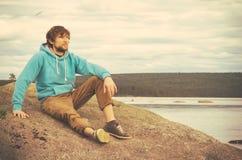 Moderno do homem novo que relaxa exterior sozinho Foto de Stock Royalty Free