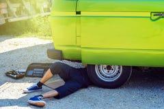 Moderno masculino novo que encontra-se abaixo de sua camionete de campista velha do temporizador que tenta repará-la ao lado da e imagem de stock