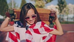 Moderno moreno de sorriso feliz bonito nos óculos de sol no parque do patim envolvido na bandeira americana e que guarda o longbo filme