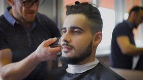 Moderno novo, corajoso em sua barbearia favorita Mestre contratado em sua barba, usos um ajustador dar forma de acordo com vídeos de arquivo
