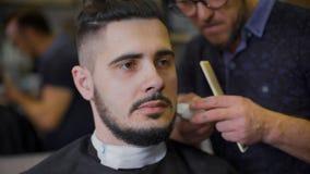 Moderno novo, corajoso em sua barbearia favorita Mestre contratado em sua barba, usos um ajustador dar forma de acordo com video estoque