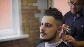 Moderno novo, corajoso em sua barbearia favorita Mestre contratado em sua barba, usos um ajustador dar forma de acordo com filme