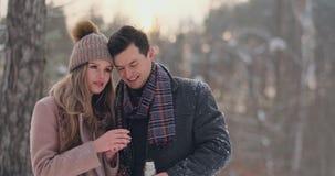 Modernos bonitos e à moda do homem e da mulher dos pares em um chá da bebida do revestimento e do lenço de uma garrafa térmica na filme