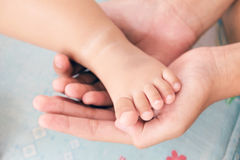 Moderns hand vaggar foten av en behandla som ett barn Arkivfoton
