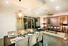 Modernt äta middag område med stolar och exponeringsglas under hängande ljus royaltyfri fotografi