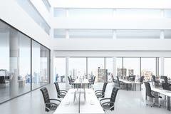 Modernt öppet utrymmekontor med stort fönster och möblemang Arkivfoto
