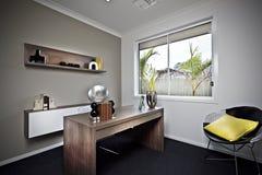 Modernt arbetsrum med trätabellen och utsmyckade objekt royaltyfri bild