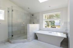 Modernt badrum med duschen och badkaret Arkivfoton