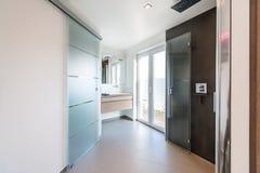 Modernt badrum med exponeringsglasdörrar och duschkabinen fotografering för bildbyråer