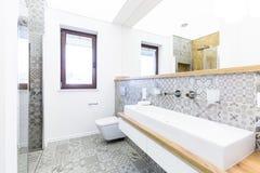 Modernt badrum med mönstrade tegelplattor royaltyfria bilder