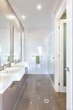 Modernt badrum med uppsättningen av lavoarer och badrummet arkivbilder