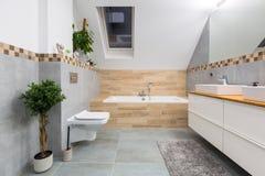 Modernt badrum som är inre med gråa tegelplattor arkivfoton