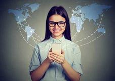 Modernt begrepp för kommunikationsteknologi Den lyckliga kvinnan med smartphonen förband att bläddra internet över hela världen Royaltyfri Bild