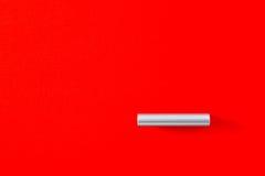 Modernt cylindriskt metallhandtag på ett rött kabinett royaltyfri fotografi