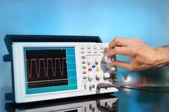 Modernt elektroniskt oscilloskop på abstrakt bakgrund Arkivbild